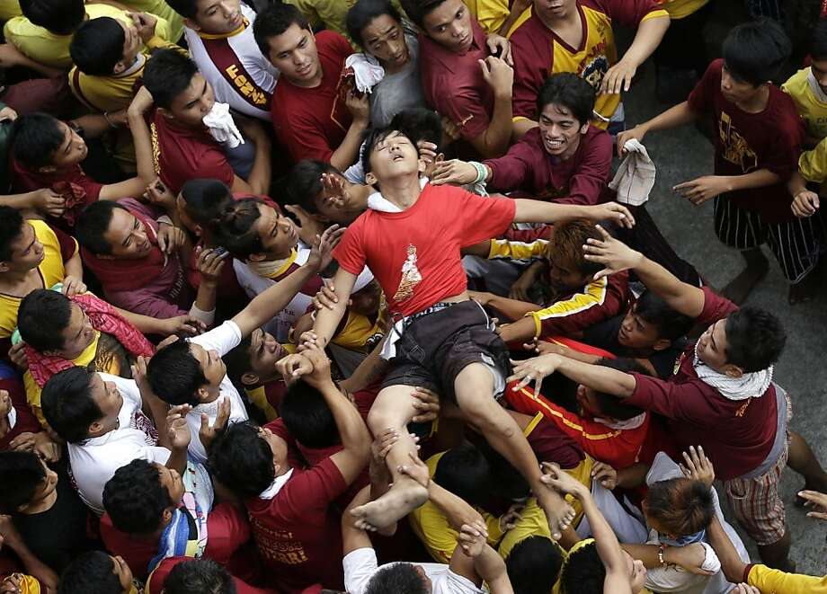 Blackout Nazarene: A Catholic devotee who fainted during a raucous procession of the centuries-old Black Nazarene statue is crowd-surfed to an ambulance in Manila. Throngs poured into the Philippine capital to see the icon of Christ, which many believe can perform miracles. Photo: Bullit Marquez, Associated Press