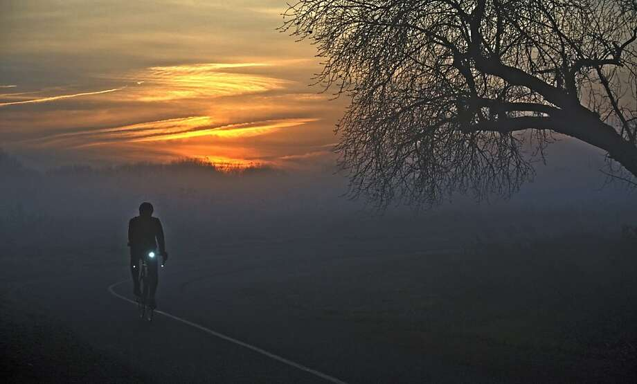 A cyclist heads west along the American River Parkway bike trail near the Capitol City Freeway underpass Tuesday morning, Jan. 8, 2013,  as the sun rises over foggy Sacramento, Calif. Photo: Tim Reese, Associated Press