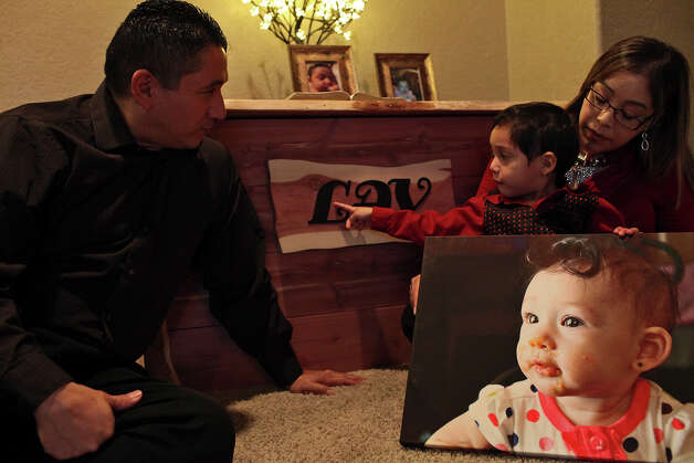 Antonio and Paula Villarreal, with their son, Jace, 3, sit with a photograph of their daughter, Laura, at their San Antonio home. Six-month-old Laura died in December, shortly after the discovery of an aggressive brain tumor. Money is being raised at GiveForward.com to help offset Laura's medical bills. Photo: Lisa Krantz, San Antonio Express-News / © 2012 San Antonio Express-News