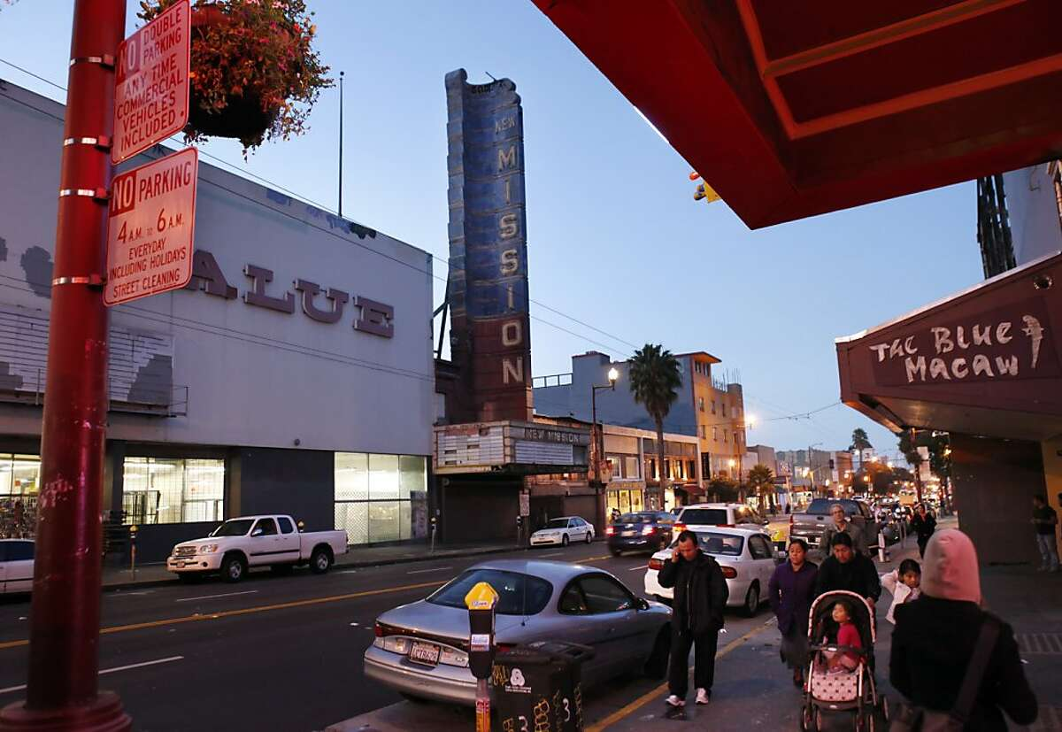 Pedestrians walk across the street from the New Mission Theater on Mission Street in San Francisco, Calif., on Tuesday, January 8, 2013. Plans are in the works to remodel the historic New Mission Theater into a five-plex Alamo Alehouse Cinema. The project, which is before the planning commission, also calls for demolishing the aging, battered Giant Value store next door to the old theater and replacing it with market rate condos.