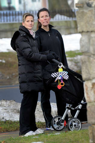Out for a morning walk, Alison Brown, left, pushing baby Parker, 13-months-old, and Stacey Mullins, stop to watch the first excavator strives into the old Ridgefield Library, Wednesday morning, January 9, 2013. Photo: Carol Kaliff / The News-Times