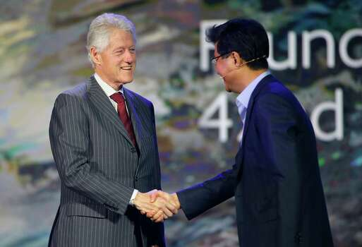 Former President Bill Clinton, left, shakes hands with Dr. Stephen Woo, president of Samsung Electronics' Device Solutions, during Samsung's keynote address at the International Consumer Electronics Show in Las Vegas, Wednesday, Jan. 9, 2013. (AP Photo/Jae C. Hong) Photo: Jae C. Hong, Associated Press / AP