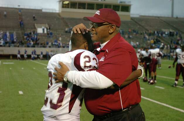 Central head coach Andrew Washington, left,  comforts one of his players, senior running back Keith O'Neal, after the Jaguars 44-22 loss to the Friendswood Mustangs in the third round of playoffs at Baytown's Stallworth Stadium on Saturday.  Valentino Mauricio/The Enterprise Photo: Valentino Mauricio / Beaumont