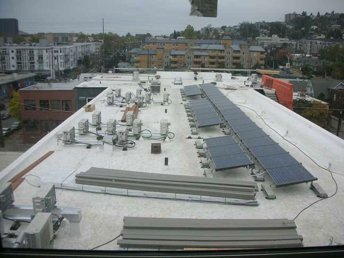 Rooftop solar power panels of Stream Uptown, a new lower Queen Anne apartment building that boasts of being the first residential building in Seattle to fully mitigate its carbon footprint for construction, and ongoing operation and maintenance.