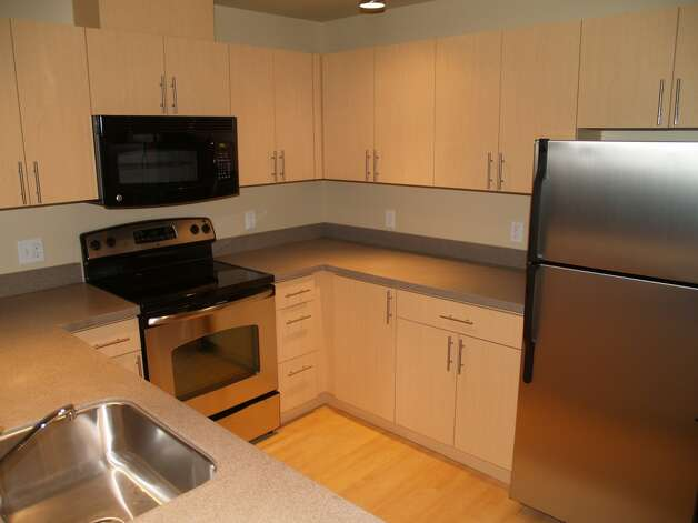 An apartment kitchen in Stream Uptown, a new lower Queen Anne apartment building that boasts of being the first residential building in Seattle to fully mitigate its carbon footprint for construction, and ongoing operation and maintenance. Photo: Stream Real Estate LLC