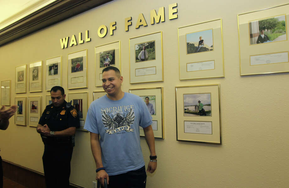 San Antonio police officer Jonathan Esquivel,29, (center) beams after a ceremony held in Esquivel's honor Wednesday January 9, 2013 at Warm Springs Rehabilitation Hospital. Esquivel, a six-year San Antonio police veteran, was hit by a truck while working at an accident scene last year and has been recuperating ever since. Esquivel was honored by Warm Springs with a place on their Wall of Fame. Photo: JOHN DAVENPORT, San Antonio Express-News / ©San Antonio Express-News/Photo Can Be Sold to the Public