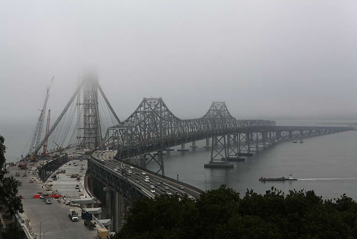 In this file photo, fog hovers over the new and present eastern side of the bay bridge in San Francisco.