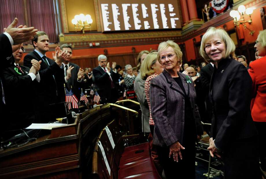 "Newtown First Selectwoman Pat Llodra, center left, and Newtown School Superintendent  Dr. Janet Robinson, center right, receive a standing ovation inside the Hall of the House during Gov. Dannel P. Malloy's State of the State address the at the Capitol in Hartford, Conn., Wednesday, Jan. 9, 2013. Malloy urged state lawmakers Wednesday to work with him to prevent future tragedies like the Sandy Hook Elementary School shooting, but stressed that ""more guns are not the answer.""  Legislators also must grapple with a projected deficit of about $1.2 billion. (AP Photo/Jessica Hill) Photo: Jessica Hill, Associated Press / FR125654 AP"
