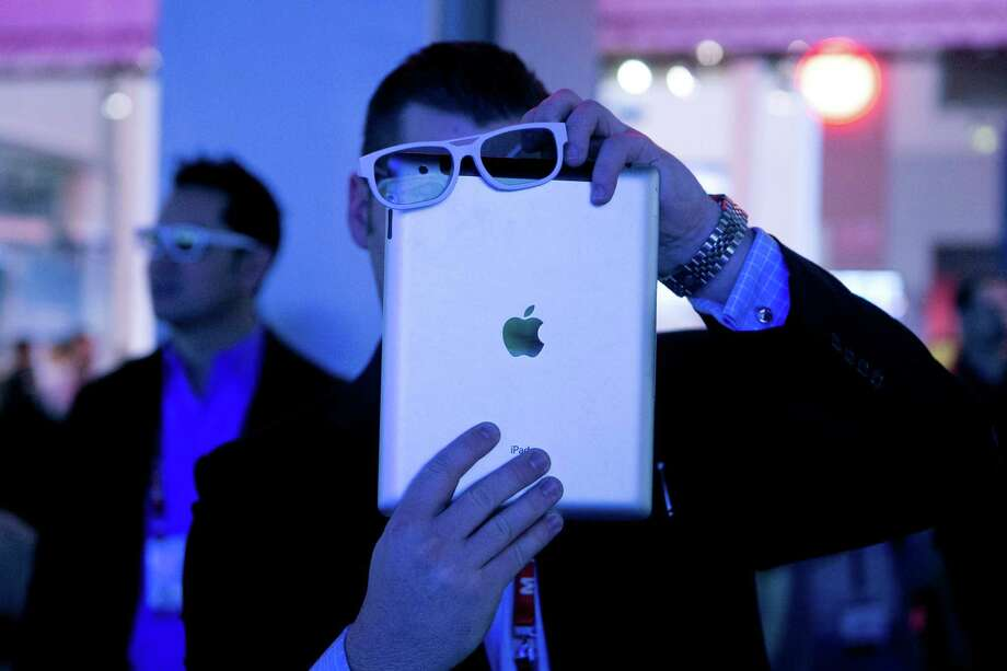Attendee Cade Madison takes a video of the LG Electronics Inc. 3D video wall using 3D glasses over his Apple Inc. iPad during the 2013 Consumer Electronics Show in Las Vegas, Nevada, U.S., on Wednesday, Jan. 9, 2013. The 2013 CES trade show, which runs until Jan. 11, is the world's largest annual innovation event that offers an array of entrepreneur focused exhibits, events and conference sessions for technology entrepreneurs. Photographer: Andrew Harrer/Bloomberg *** Local Caption *** Cade Madison Photo: Andrew Harrer, Bloomberg / © 2013 Bloomberg Finance LP