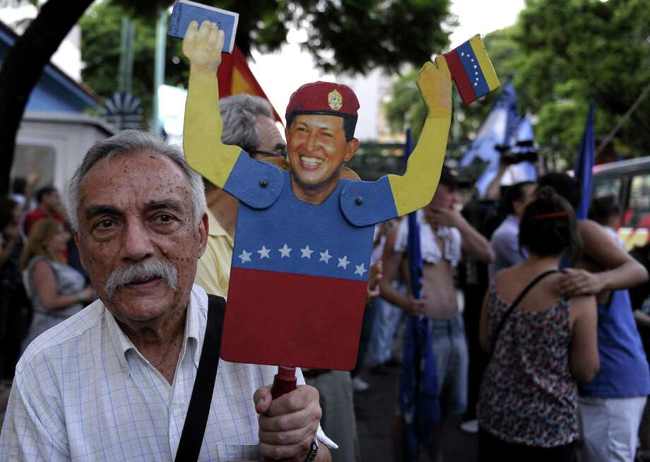 A man holds a figurine of Venezuelan President Hugo Chavez during a rally in support of his recovery in front of the Venezuelan embassy in Buenos Aires on January 8, 2013. The President of the National Assembly Diosdado Cabello announced today that due to health reasons, Chavez will not be able to take the oath to be sworn in for a fourth term in office next January 10. A constitutional fight intensified with the government planning a massive show of support in the streets on the day he is supposed to be sworn in. Chavez, who underwent his fourth round of cancer surgery in Havana nearly a month ago, is suffering from a severe pulmonary infection that has resulted in a respiratory insufficiency. AFP PHOTO / ALEJANDRO PAGNIALEJANDRO PAGNI/AFP/Getty Images Photo: ALEJANDRO PAGNI, AFP/Getty Images / AFP