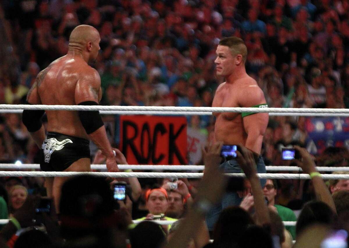 """Dwyane """"The Rock"""" Johnson, left, and John Cena face off in Miami at WrestleMania XXVIII in 2012. Both men will appear in Houston for WWE's 20th anniversary."""