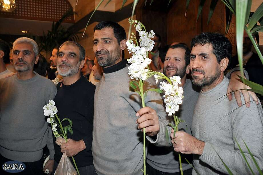 Iranian men captured by Syrian rebels in August hold flowers given to them by Shiite clerics after being freed in Damascus. Photo: Hopd, Associated Press