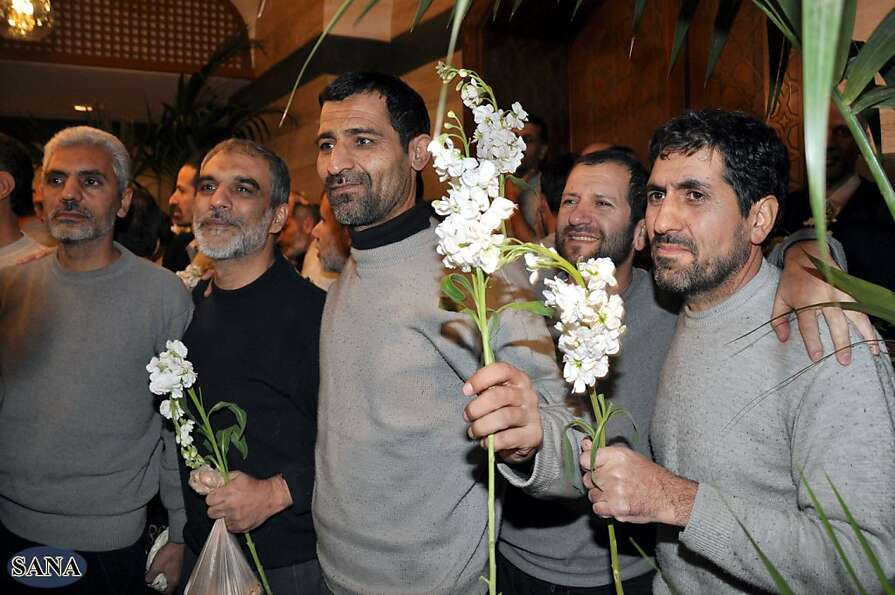Iranian men captured by Syrian rebels in August hold flowers given to them by Shiite clerics after b