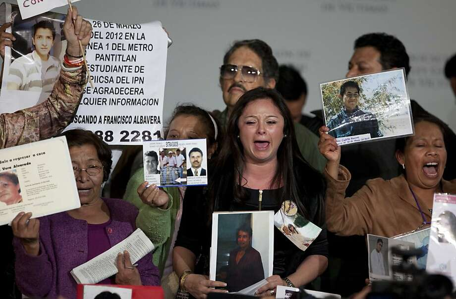 People hold up images of alleged victims as they demonstrate at the event where President Enrique Peña Nieto OKd the law. Photo: Eduardo Verdugo, Associated Press