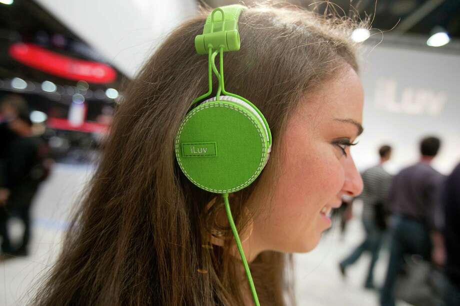 "Attendee Abigail Forman demonstrates the iLuv Creative Technology ""ReF"" headphones during the 2013 Consumer Electronics Show in Las Vegas on Wednesday, Jan. 9. Photo: Andrew Harrer, Bloomberg / © 2013 Bloomberg Finance LP"