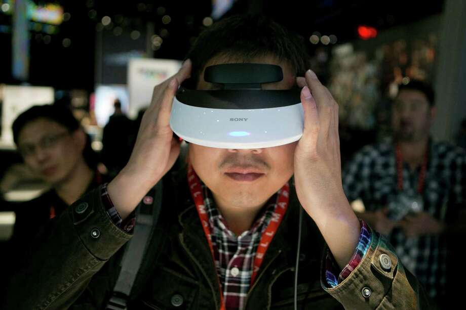 Attendee Hongqiang Bao interacts with a Sony Corp. Personal 3D Viewer headset Wednesday. Sony Corp. is enabling its Bravia TVs, Handycam camcorders and Xperia phones to communicate with each other as Chief Executive Officer Kazuo Hirai tries to end four years of losses. Photo: Andrew Harrer, Bloomberg / © 2013 Bloomberg Finance LP