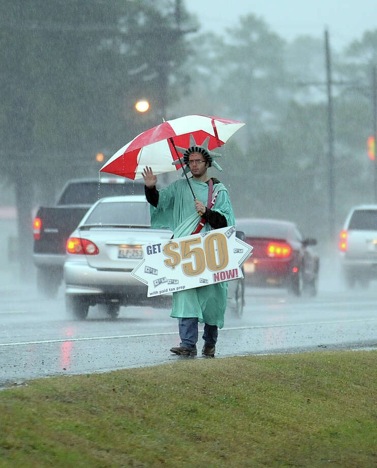 An employee of Liberty Tax Service on Main Street in Lumberton waves on patrons during the flash flood warnings in Jefferson County on Wednesday, January 9, 2013. Photo taken: Randy Edwards/The Enterprise