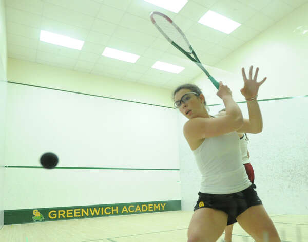 Greenwich Academy senior Maria Ubina, foreground, hits against Maggie O'Neill of Taft during squash match at Greenwich Academy, Wednesday, Jan. 9, 2013. Photo: Bob Luckey / Greenwich Time