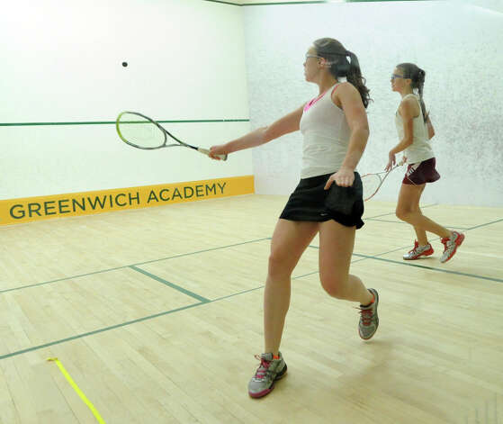 Greenwich Academy senior Lindsey Scott, foreground, hits against Eleanor Carroll of Taft during squash match at Greenwich Academy, Wednesday, Jan. 9, 2013. Photo: Bob Luckey / Greenwich Time
