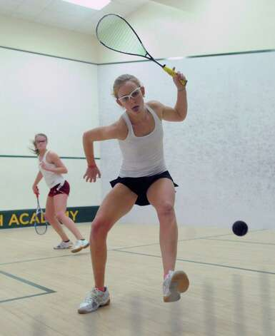 Kayley Leonard of Greenwich Academy, foreground, hits against Eliza Dunham of Taft, during squash match at Greenwich Academy, Wednesday, Jan. 9, 2013. Photo: Bob Luckey / Greenwich Time