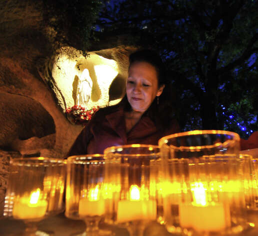 Patricia Doria turns on electric candles Wednesday to honor the 26 victims of the Newtown shooting. Photo: Robin Jerstad, Special To The Express-News