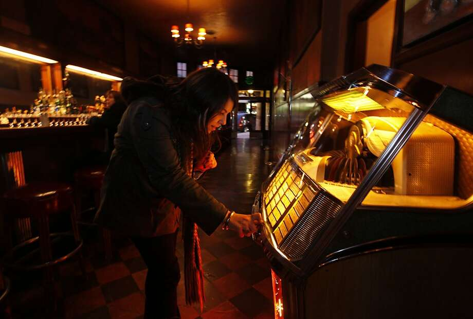 Devin Mantalto chooses songs on the jukebox at Tosca Cafe. New owners will keep the old-style ambience but add food. Photo: Michael Macor, The Chronicle