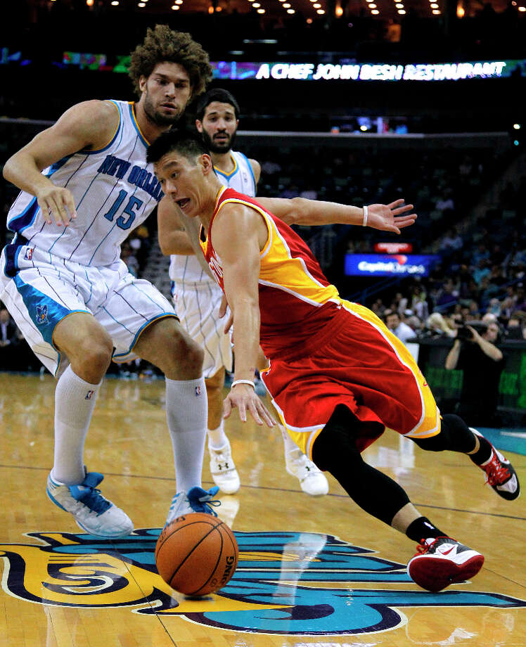 Rockets point guard Jeremy Lin, front right, drives past Hornets center Robin Lopez. Photo: Jonathan Bachman, Associated Press / FR170615 AP