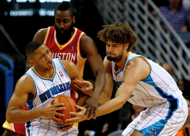 Hornets center Robin Lopez, right, hands the ball to shooting guard Eric Gordon, left, as Rockets shooting guard James Harden, center, defends. Photo: Jonathan Bachman, Associated Press / FR170615 AP