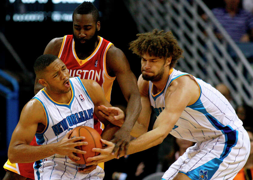 Hornets center Robin Lopez, right, hands the ball to shooting guard Eric Gordon, left, as Rockets sh