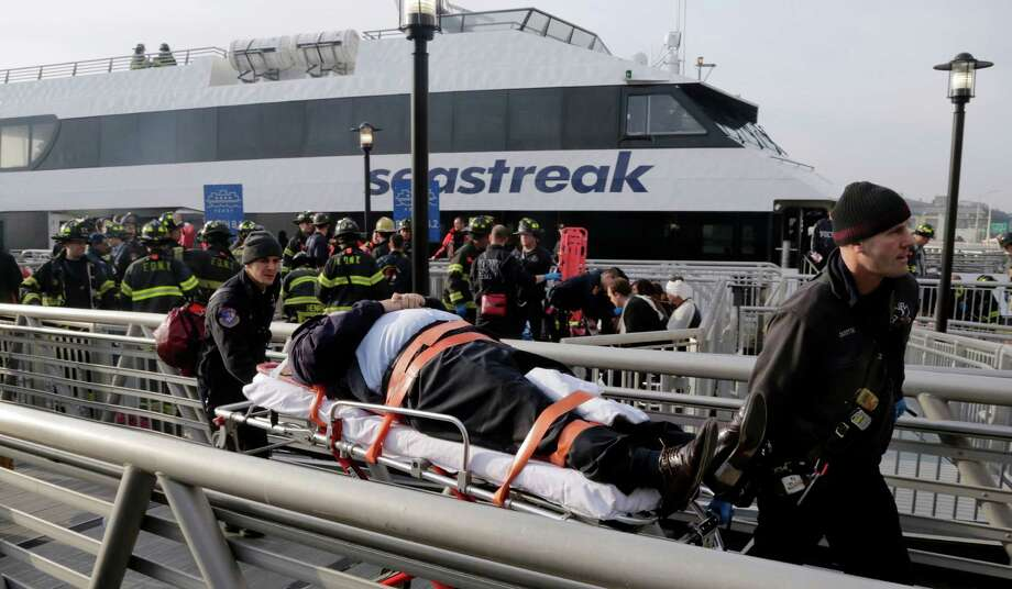 An injured passenger from the Seastreak Wall Street ferry is taken to an ambulance, in New York,  Wednesday, Jan. 9, 2013. The ferry from Atlantic Highlands, N.J., banged into the mooring as it arrived at South Street in lower Manhattan during morning rush hour, injuring as many as 50 people, at least one critically, officials said.(AP Photo/Richard Drew) Photo: Richard Drew