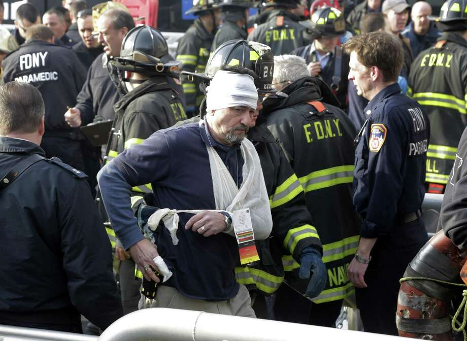 An injured passenger of the Seastreak Wall Street ferry is aided by New York City firefighters, in New York,  Wednesday, Jan. 9, 2013. The ferry from Atlantic Highlands, N.J., banged into the mooring as it arrived at South Street in lower Manhattan during morning rush hour, injuring as many as 50 people, at least one critically, officials said. (AP Photo/Richard Drew) Photo: Richard Drew