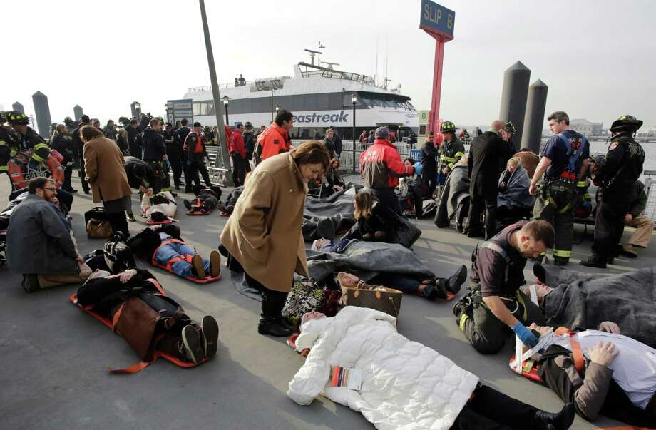 Victims of the Seastreak Wall Street ferry accident are aided by rescue personnel, Wednesday, Jan. 9, 2013 in New York. The ferry, rear, from New Jersey made a hard landing at the dock as it pulled up to lower Manhattan during Wednesday morning rush hour, injuring as many as 50 people, at least one critically, officials said. (AP Photo/Mark Lennihan) Photo: Mark Lennihan