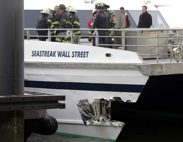 New York City firefighters walk the deck of the Seastreak Wall Street ferry in New York,  Wednesday, Jan. 9, 2013. The ferry from Atlantic Highlands, N.J., banged into the mooring as it arrived at South Street in lower Manhattan during morning rush hour, injuring as many as 50 people, at least one critically, officials said.(AP Photo/Richard Drew) Photo: Richard Drew