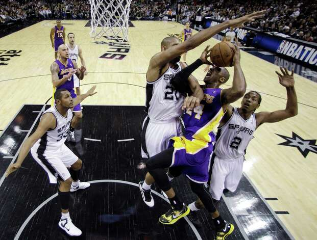 Los Angeles Lakers' Kobe Bryant (24) is blocked by San Antonio Spurs' Tim Duncan (21) and Kawhi Leonard (2) as he drives to the basket during the first quarter of an NBA basketball game on Wednesday, Jan. 9, 2013, in San Antonio. (AP Photo/Eric Gay) Photo: Eric Gay