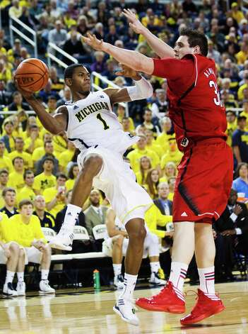 Michigan forward Glenn Robinson III (1) tries to keep the ball inbounds under pressure from Nebraska center Andre Almeida, right, in the second half of an NCAA college basketball game, Wednesday, Jan. 9, 2013, at Crisler Center in Ann Arbor, Mich. Michigan won 62-47. (AP Photo/Tony Ding) Photo: Tony Ding