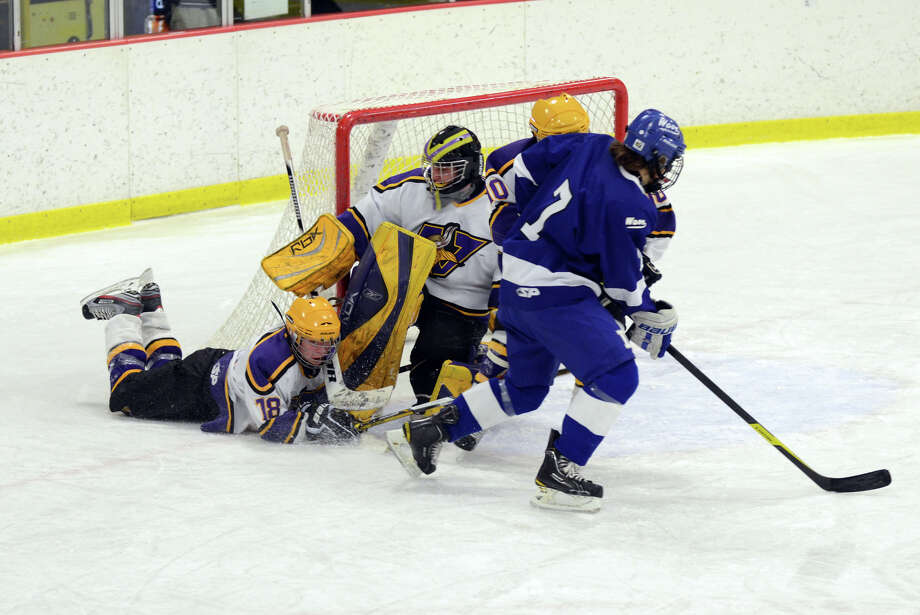 Westhill's Dan Rotkewicz (18) gets caught up in Westhill goalie Tyler Phillipson's defense against Darien's Jack Knowlton (7)  during the boys hockey game at Terry Connors Rink in Stamford on Wednesday, Jan. 9, 2013. Photo: Amy Mortensen / Connecticut Post Freelance
