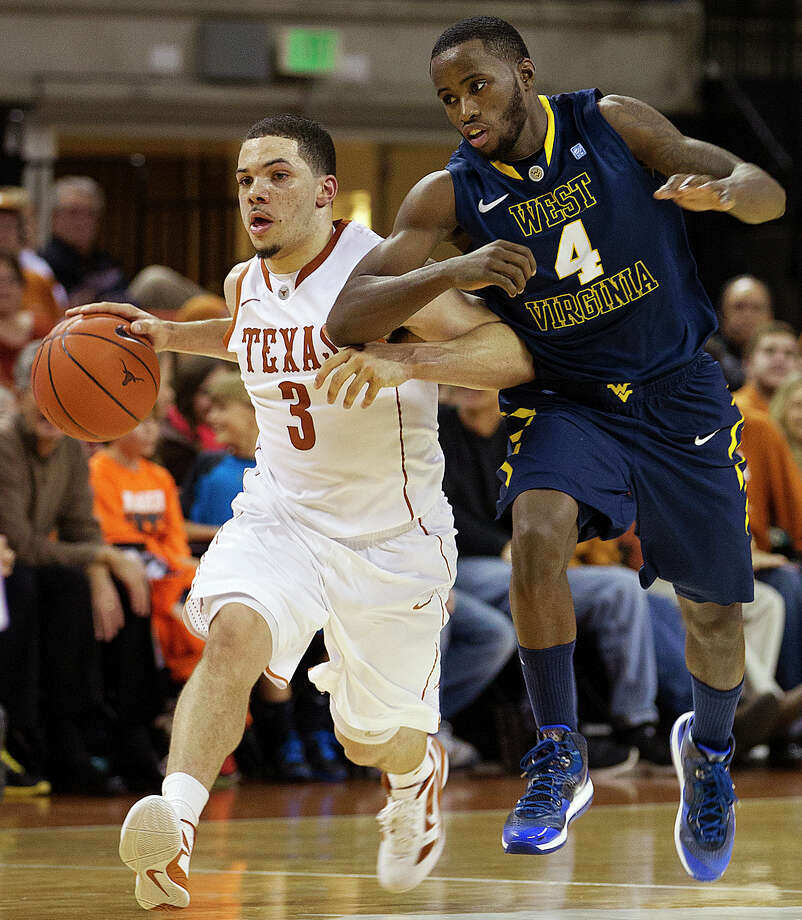 Javan Felix (left), pressured by West Virginia's Jabarie Hinds during the first half, played a game-high 42 minutes for UT in Wednesday's losing effort. He had 11 points and four assists. Photo: Alberto Martinez, AP Photo / Statesman.com / Statesman.com