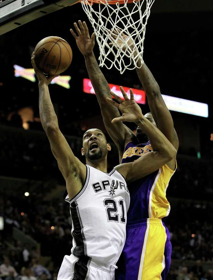 Spurs' Tim Duncan (21) scores a basket against Los Angeles Lakers' Earl Clark (06) in the first half at the AT&T Center on Wednesday, Jan. 9, 2013. Photo: Kin Man Hui, San Antonio Express-News / © 2012 San Antonio Express-News
