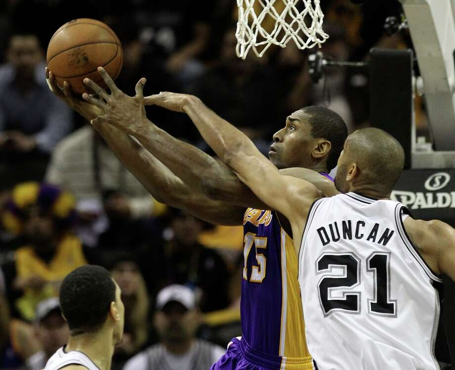 Spurs' Tim Duncan (21) reaches to attempt a block against Los Angeles Lakers' Metta World Peace (15) in the first half at the AT&T Center on Wednesday, Jan. 9, 2013. Photo: Kin Man Hui, San Antonio Express-News / © 2012 San Antonio Express-News