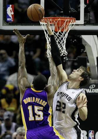 Spurs' Tiago Splitter (22) reaches for a block against Los Angeles Lakers' Metta World Peace (15) in the first half at the AT&T Center on Wednesday, Jan. 9, 2013. Photo: Kin Man Hui, San Antonio Express-News / © 2012 San Antonio Express-News