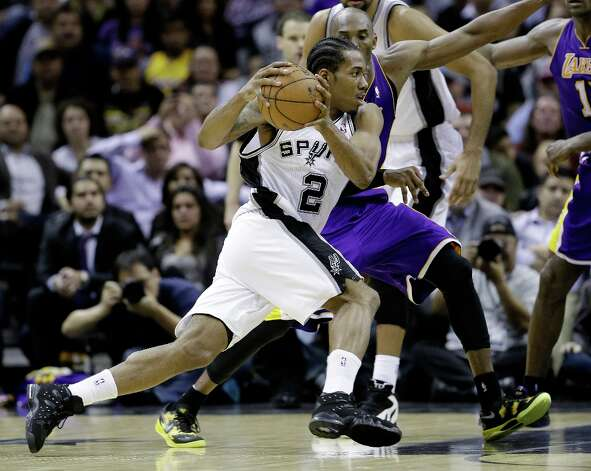 San Antonio Spurs' Kawhi Leonard (2) reaces around Los Angeles Lakers' Kobe Bryant, right, during the fourth quarter of an NBA basketball game on Wednesday, Jan. 9, 2013, in San Antonio. San Antonio won 108-105. Photo: Eric Gay, Associated Press / AP