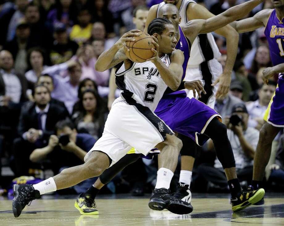 San Antonio Spurs' Kawhi Leonard (2) reaces around Los Angeles Lakers' Kobe Bryant, right, during the fourth quarter of an NBA basketball game on Wednesday, Jan. 9, 2013, in San Antonio. San Antonio won 108-105. Photo: Eric Gay, Associated Press / AP