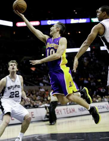Los Angeles Lakers' Steve Nash (10) shoots as San Antonio Spurs' Tiago Splitter (22), of Brazil, and Gary Neal, right, defend during the third  quarter of an NBA basketball game on Wednesday, Jan. 9, 2013, in San Antonio. San Antonio won 108-105. Photo: Eric Gay, Associated Press / AP