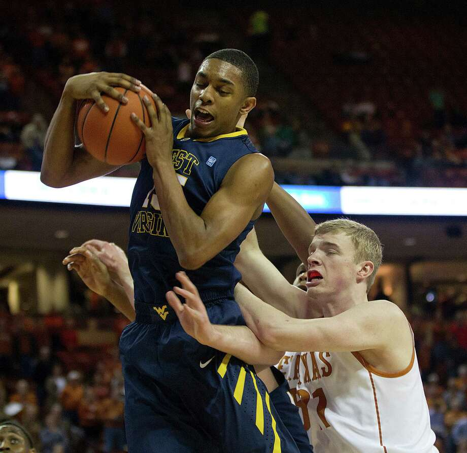 West Virginia's Terry Henderson, left, beats Texas' Connor Lammert to a rebound during the first half Wednesday night in Austin. The Mountaineers put together a 45-39 edge in rebounding, including several key rebounds on the offensive end in overtime. Photo: Alberto Martinez, MBR / Austin American-Statesman