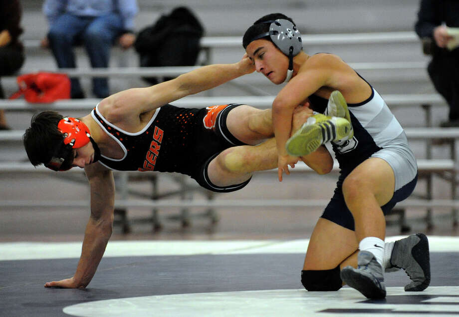 Staples' Justin Ludel, right, tries to topple Ridgefield's Jack Boscia, during wrestling action in Westport, Conn. on Wednesday January 9, 2013. Photo: Christian Abraham / Connecticut Post