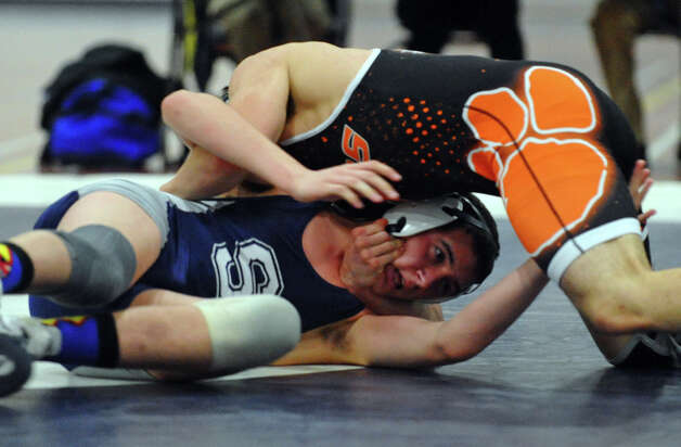 Staples' Alex Kagstad goes up against Ridgefield's Tyler Hamilton, during wrestling action in Westport, Conn. on Wednesday January 9, 2013. Photo: Christian Abraham / Connecticut Post
