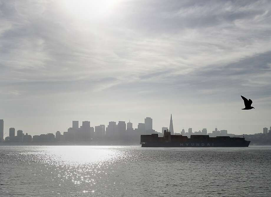A container ship passes under the Bay Bridge on its way past the San Francisco skyline. An oil tanker struck the Bay Bridge Monday January 7, 2013.  Early assessment showed minor damage and the bridge remained open. Photo: Brant Ward, The Chronicle