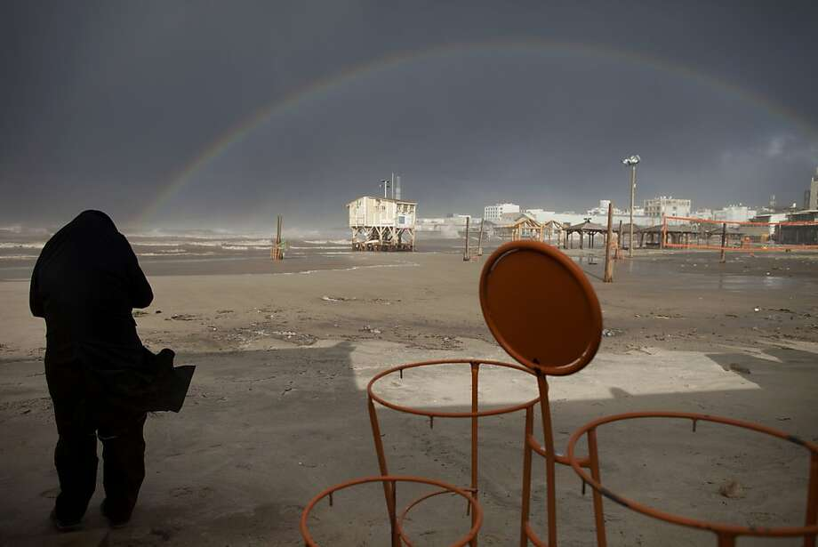 Arc over Israel: An Ultra-Orthodox Jewish man watches a rainbow over the Mediterranean Sea in Tel Aviv, Israel. A storm pounded Tel Aviv with torrential rain in one of the fiercest downpours in decades, causing widespread flooding. Photo: Oded Balilty, Associated Press
