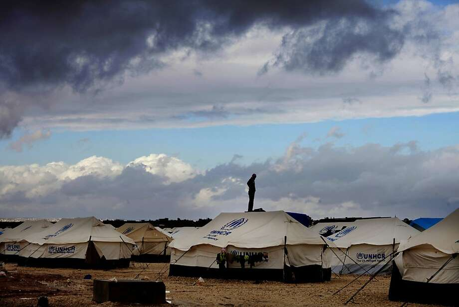 A Syrian refugee stands on top of a water tank at Zaatari refugee camp, near the Syrian border in Mafraq, Jordan, Wednesday, Jan. 9, 2013. The unusual weather was a particularly harsh blow for the vulnerable Syrian refugees, especially about 50,000 sheltering in the Zaatari tent camp in Jordan's northern desert. Torrential rains over the past four days have flooded 200 tents and forced women and infants to evacuate in temperatures below freezing at night, whipping wind and lashing rain. Photo: Mohammad Hannon, Associated Press