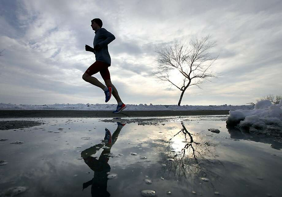 As a continuing trend of milder winter weather occupies the upper Midwest region, University of Wisconsin-Madison track and cross-country team member Michael Van Voorhis makes his way past a melting snow cover during a run along Vilas Park Drive in Madison, Wis. Tuesday, Jan. 8, 2013. Photo: John Hart, Associated Press